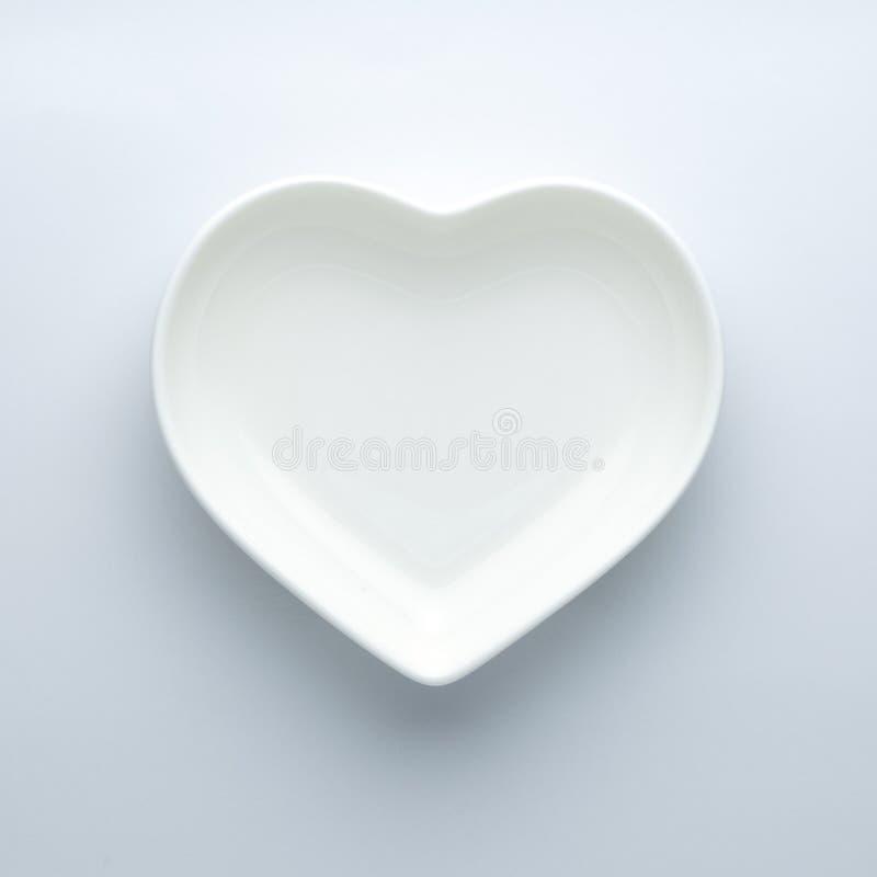 minimalism Пустая плита в форме сердца на белой предпосылке в центре рамки Современные керамические лоснистые блюда стоковые изображения rf