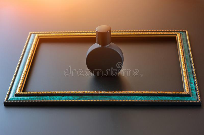 Black matte bottle for unisex perfume close-up inside emerald frame with gold border on a dark background, mock up, warm light. Minimalism and fashion royalty free stock photography