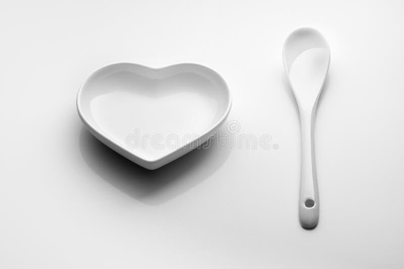 minimalism Hartschotel en ceramische lepel op een witte achtergrond Voor ontwerp op de Dag van Valentine, huwelijk, romantisch di stock foto's