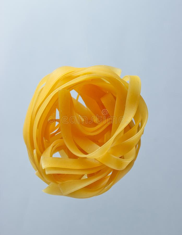 Minimalism italian food concept. Raw tagliatelle noodles on gray background stock photos