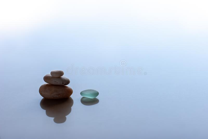 minimalism 3 pyramidkiselstenar och ett grönt exponeringsglas med reflexioner arkivbilder