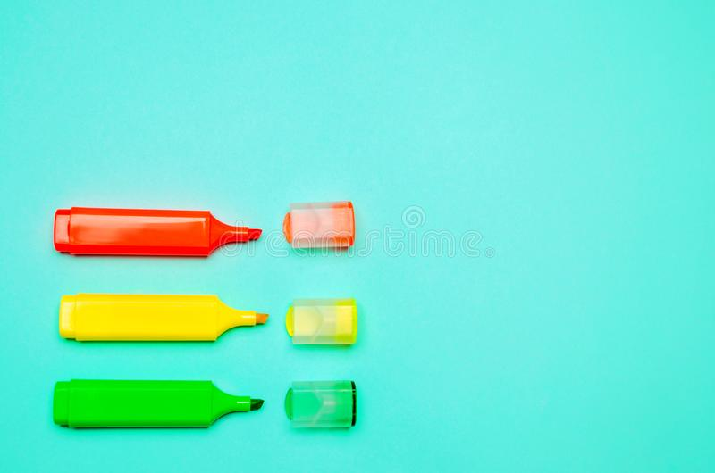 minimalism. three multicolored markers on a blue background. creativity, pin up, school stationery, school concept, space for text royalty free stock photos