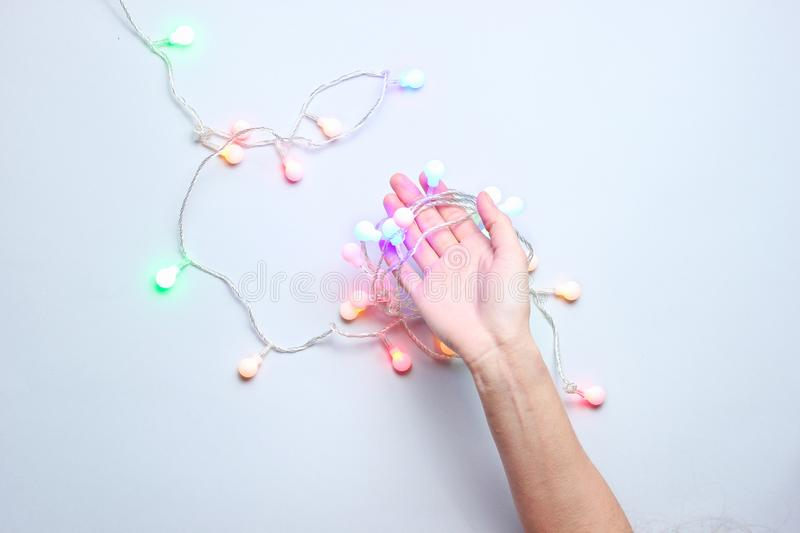 Minimalism trend. Female hand hold bright glowing led  neon garlands. On gray background. Top view royalty free stock image