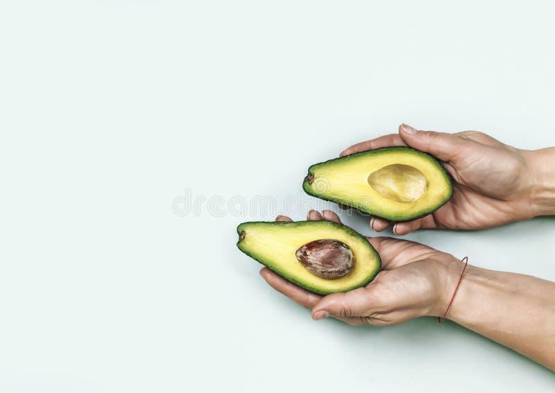 minimalism Voedsel Rijpe avocado, besnoeiing in de helft in vrouwelijke handen op een blauwe achtergrond Concept: Gezond voedsel, stock foto's