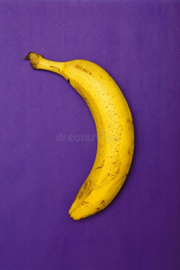 Minimalismbefruktning: banan på blå och violett bakgrund Bästa sikt, lekmanna- lägenhet royaltyfria foton