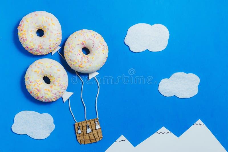 Minimalismo creativo de la comida, buñuelo en la forma del aerostato en cielo azul con las nubes, montañas, visión superior, espa imágenes de archivo libres de regalías