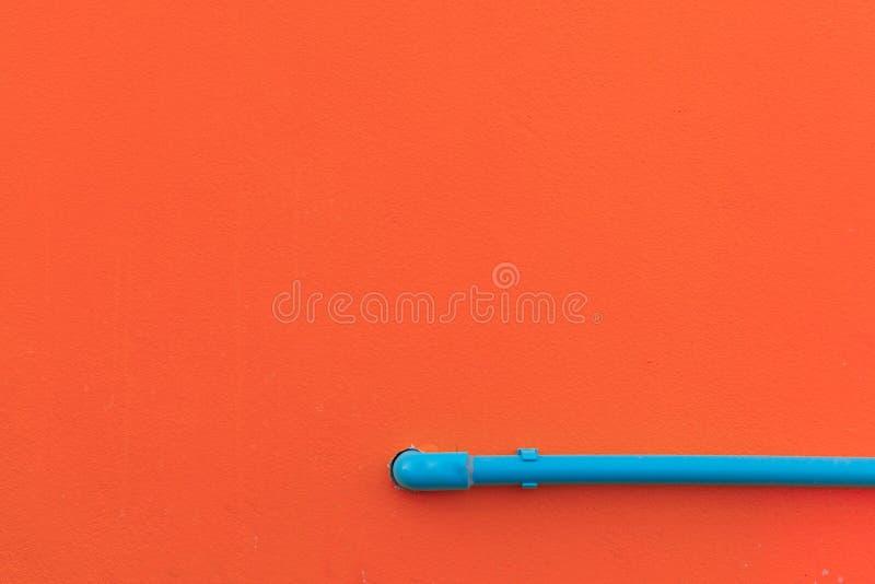 Minimalismstijl, Blauwe waterbuis op de muur stock foto