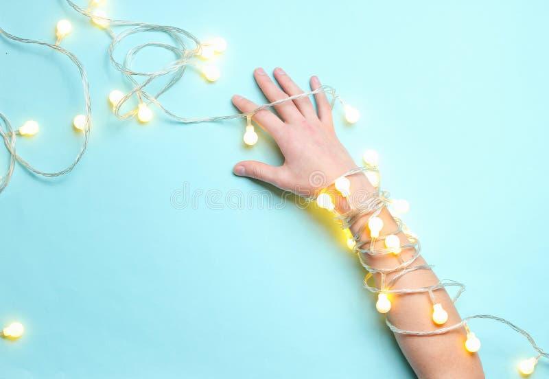 Minimalismtendens Vrouwelijke die hand met heldere lichtgevende slingers wordt verpakt stock foto