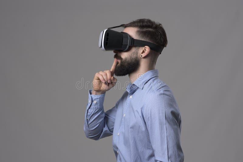Minimalismusprofilansicht von jungen Geschäftsmann tragenden vr Gläsern mit dem Finger über den Lippen, die weg copyspace betrach stockfoto