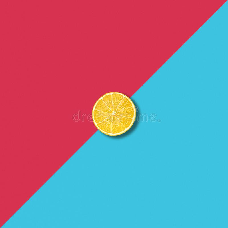Minimalist abstract with single lemon slice on vibrant colorful background stock images