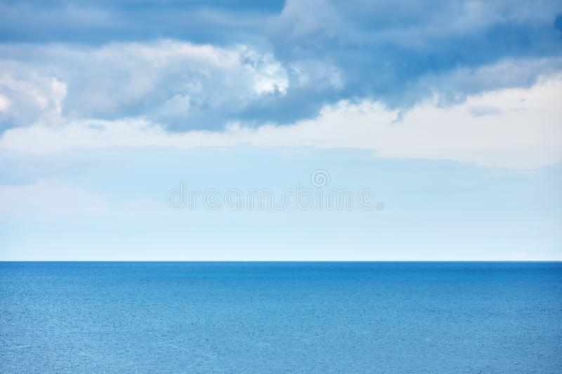 Minimalist nature landscape background with calm sea and rain clouds over the sea stock photography