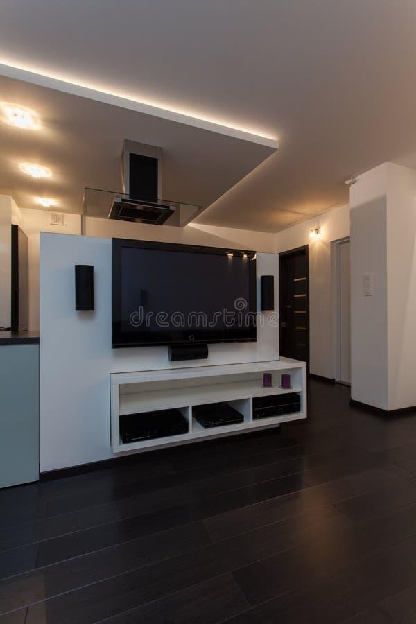 Minimalist apartment - home cinema. Minimalist apartment - modern appliances, big tv in living room stock photo