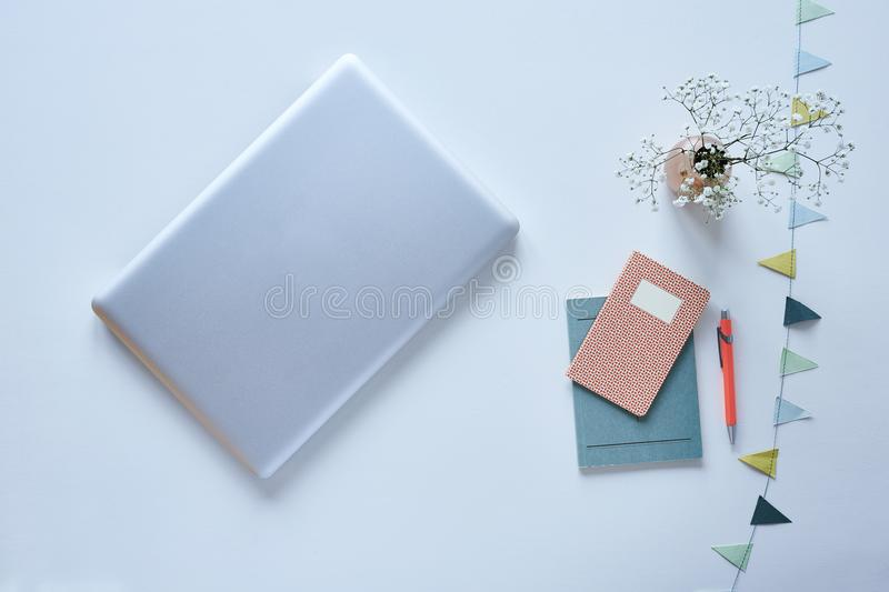 Minimalist blogger desktop laptop and pastel accessoires with flowers. Modern workspace royalty free stock images