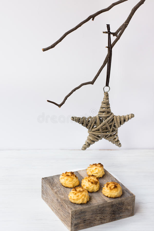 Minimalist Christmas and New Year decoration, rattan star hanging on a dry tree branch, coconut macaroons on a wood box stock photos