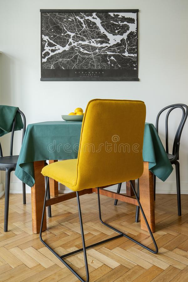 A minimalist city map poster on a white wall of a dining room interior with a yellow chair. On herringbone parquet floor stock images