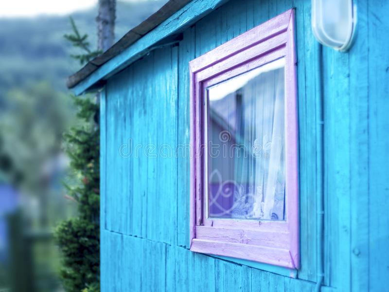 Minimalist Design Concept: Vivid Purple Window Frame, a Light on Blue Wall of Wooden Planks. Mountain Reflection in Glass, White royalty free stock photography