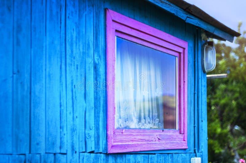 Minimalist designbegrepp: Livlig purpurfärgad fönsterram, ett ljus på den blåa väggen av träplankor Bergreflexion i exponeringsgl royaltyfria foton