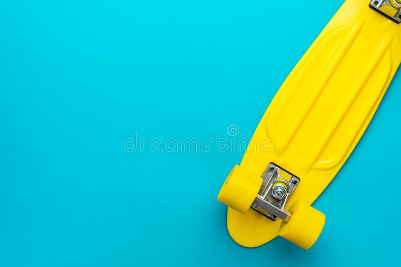 Minimalist flat lay photo of cruiser board over blue background with copy space. Minimalist flat lay photo of yellow plastic mini cruiser board on blue royalty free stock images