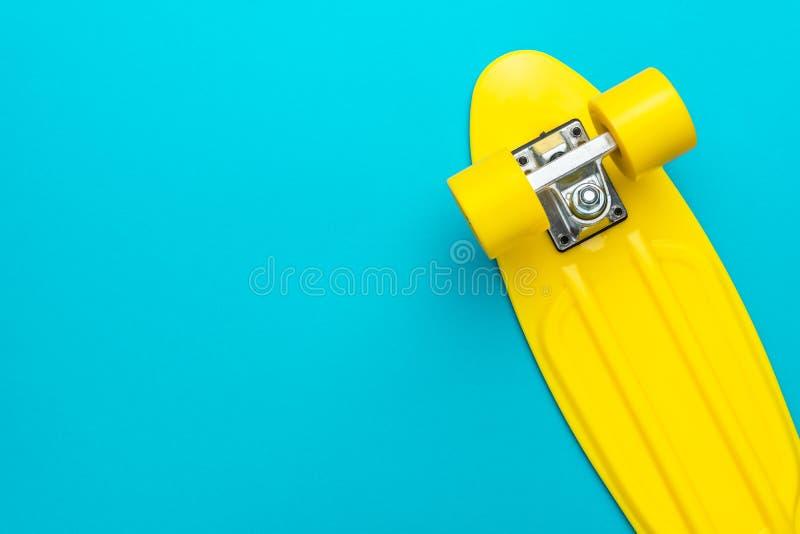 Minimalist flat lay photo of cruiser skateboard over turquoise blue background. Minimalist flat lay photo of yellow plastic mini cruiser board on blue background stock images