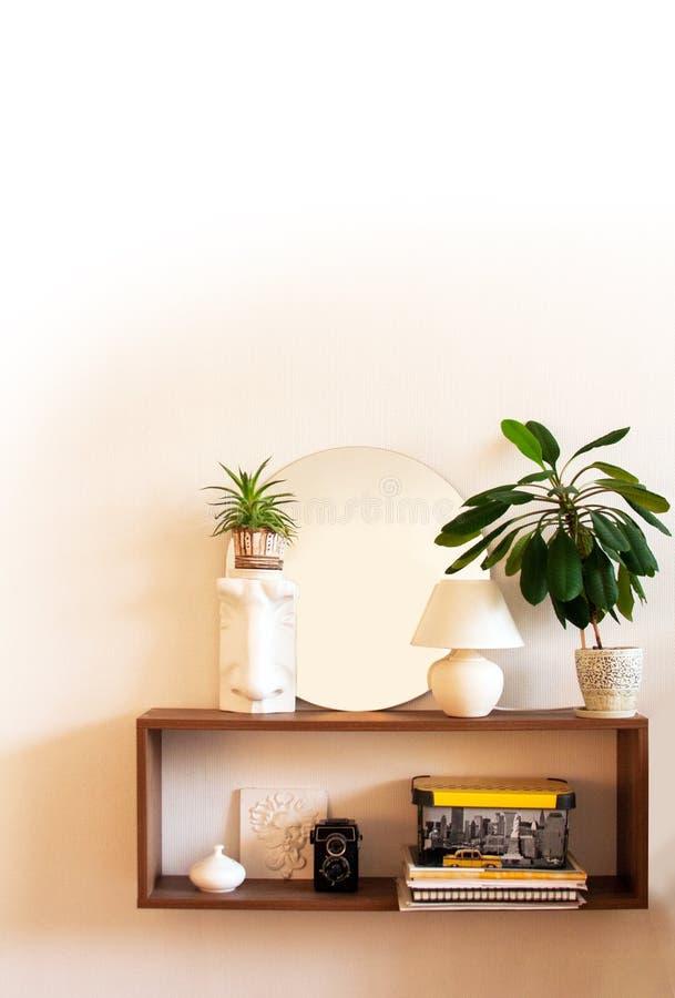 Minimalist inre vitt designrum med trähyllan, rund spegel, lampa, gröna växter, dekorativa beståndsdelar royaltyfri bild