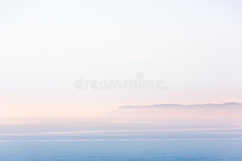 Minimalist landscape scene of Sandwich Bay, Kent on a misty but bright summer morning. royalty free stock photography