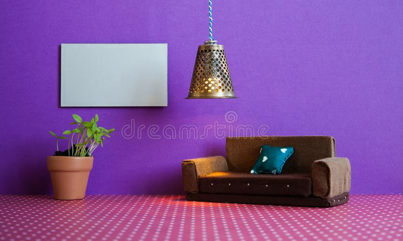 Minimalist living room furniture interior. Simple design brown sofa, flowerpot green plant and blank poster template on. Violet wall stock photography