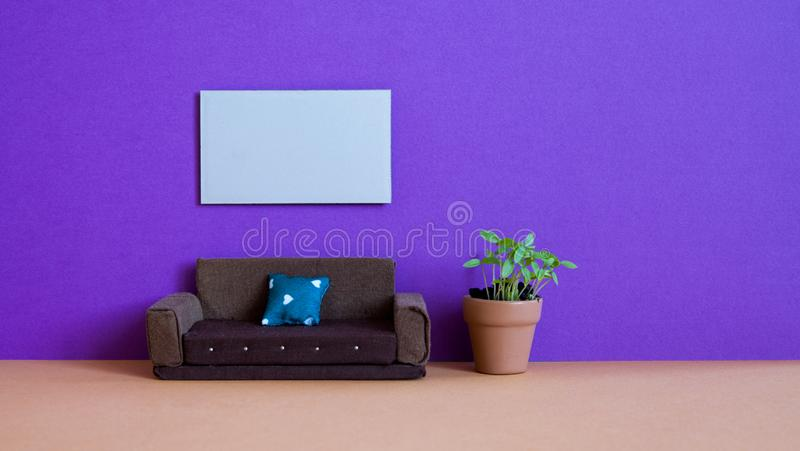 Minimalist living room furniture interior. Simple design brown sofa, flowerpot green plant and blank poster template on. Violet wall stock images