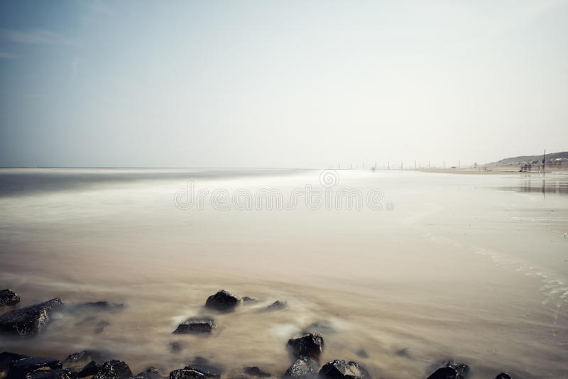 Minimalist misty seascape with rocks stock image