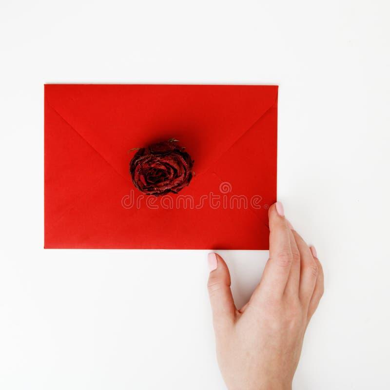 Minimalist mode- och sk?nhetfoto En förälskelsebokstav i ett rött kuvert med en ros Kvinnliga händer lägger en förälskelsebokstav royaltyfri bild