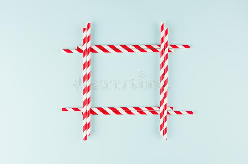 Minimalist modern art abstract background - red striped straws on light soft mint colors paper as blank square frame. Minimalist modern art abstract background stock photos