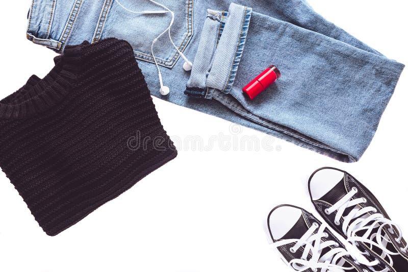 Minimalist och trendig kvinnlig dräkt - jeans, svarta gymnastikskor, sweatern, hörlurar och rött spikar polerar isolerat fotografering för bildbyråer