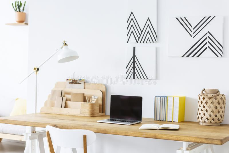 Minimalist paintings on a white wall above a wooden desk with a laptop and notebooks in a scandinavian home office interior. Real. Photo. concept royalty free stock images