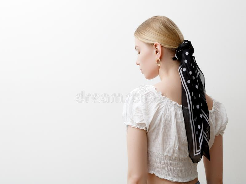 Minimalist photo, Fashionable girl in stylish summer things . View from the back. Earrings, a ring , a scarf on her head royalty free stock image