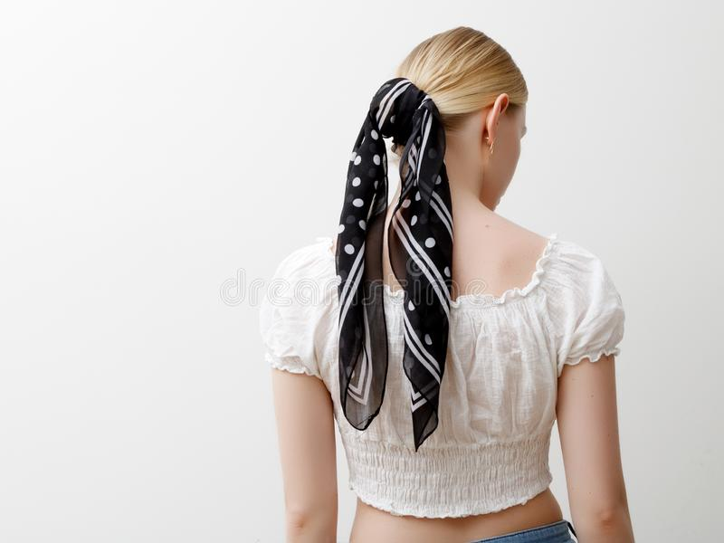 Minimalist photo, Fashionable girl in stylish summer things . View from the back. Earrings, a ring , a scarf on her head stock photo