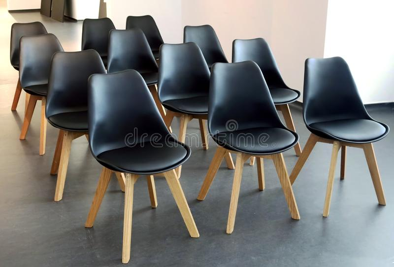 Minimalist Scandinavian design of conference room. Rows of black chairs in meeting room. Seats for participants stock photo