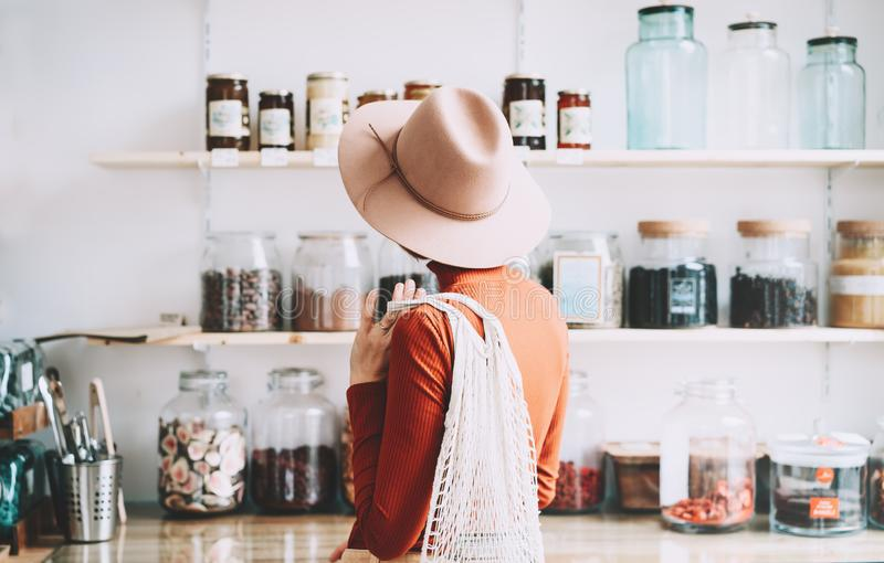 Young woman in zero waste shop or plastic free store stock image