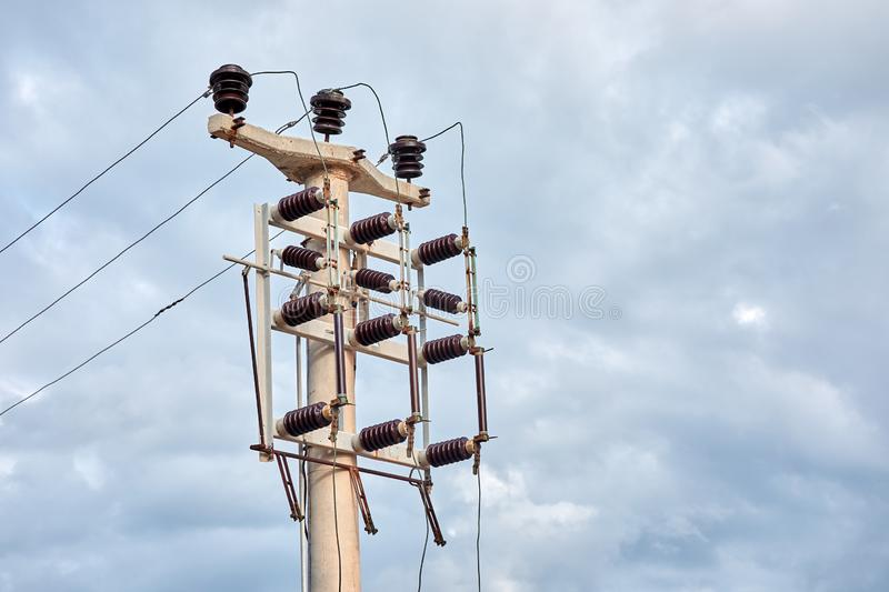 Minimalist view of a concrete high voltage power electric pole, power lines and fuses stock images