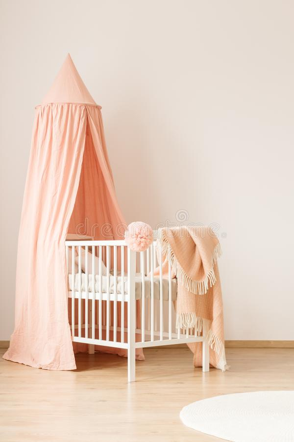 White crib by empty wall. Minimalist, white crib with a pastel pink canopy for a baby girl by a white, empty wall in a cute, modern nursery room interior stock photography