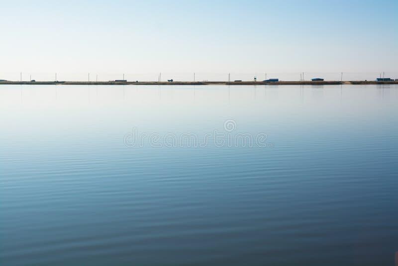 Minimalistic与路的水风景在湖岸 库存照片