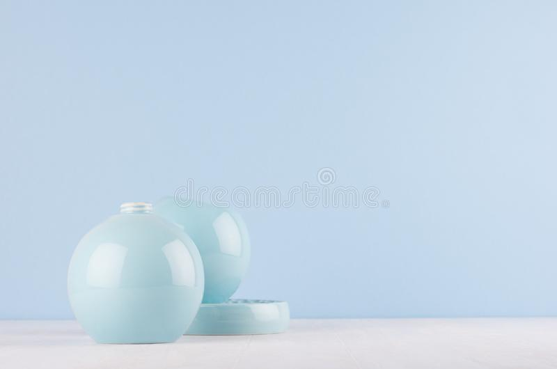 Minimalistic在时髦淡色浅兰的颜色的家装饰-陶瓷球形花瓶和碗在白色木背景 图库摄影