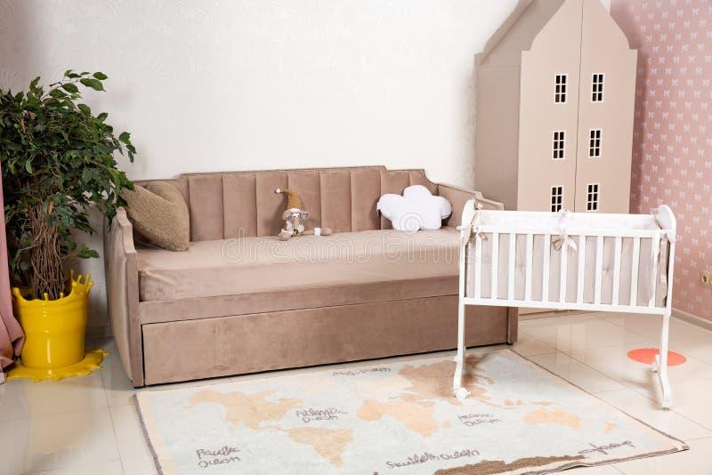 Minimalistic婴孩的与典雅的儿童的床的室妈妈的内部和沙发 免版税库存图片