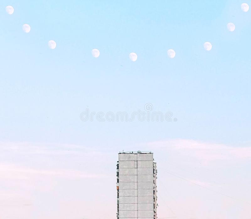 Minimalistic abstract surreal photoshopped photo of architecture. Concrete soviet house with a necklace of moons above royalty free stock photography