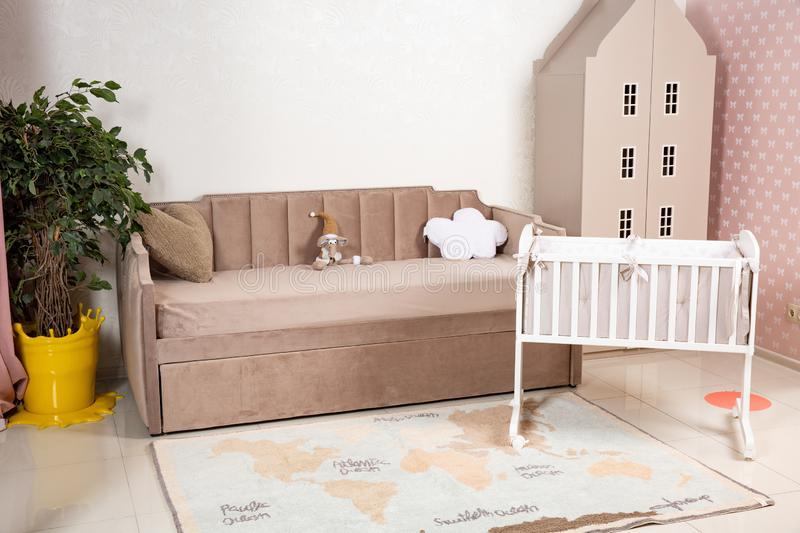 Minimalistic baby`s room interior with an elegant child`s bed and sofa for mom royalty free stock images