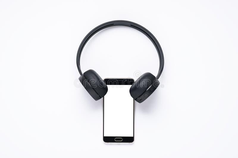 Minimalistic begrepp av grejer för musikvänner, smartphone med den vita skärmen med trådlös hörlurar orientering för apps fotografering för bildbyråer