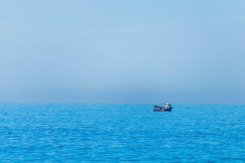 Minimalistic bild av havet med en fiskebåt Blått havsvatten och klar himmel royaltyfri bild