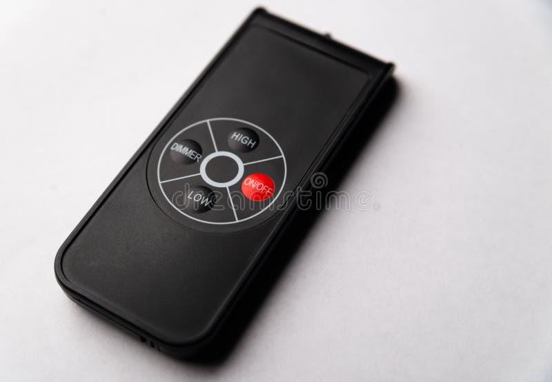 Minimalistic black remote control on white backgorund stock photos
