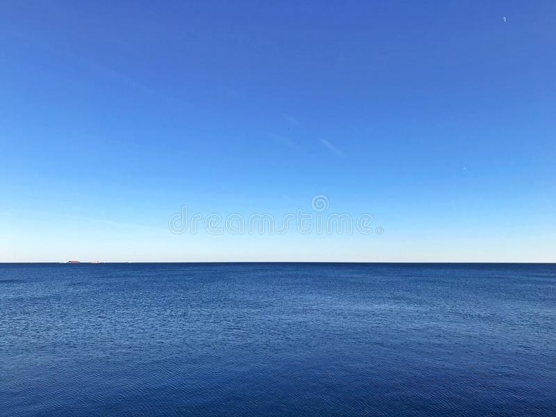 Minimalistic blue seascape with clear contrast horizon and still water royalty free stock photo