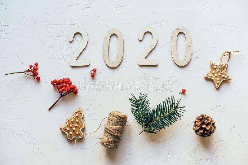 Minimalistic Christmas flat lay on a white background with simple baubles and wooden numbers 2020. Festive concept stock photography