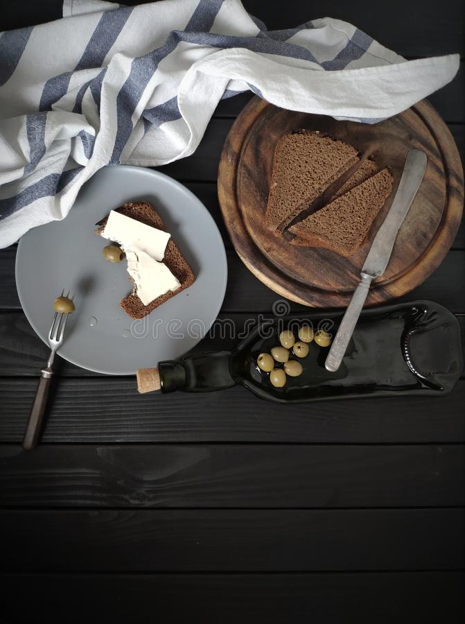 Minimalistic composition on a black wooden background, black bread, oil and olives. On the original tableware next to a natural towel stock photography