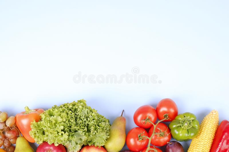 Minimalistic composition with buch of fresh organic mixed fruits and vegetables on light blue background. stock image